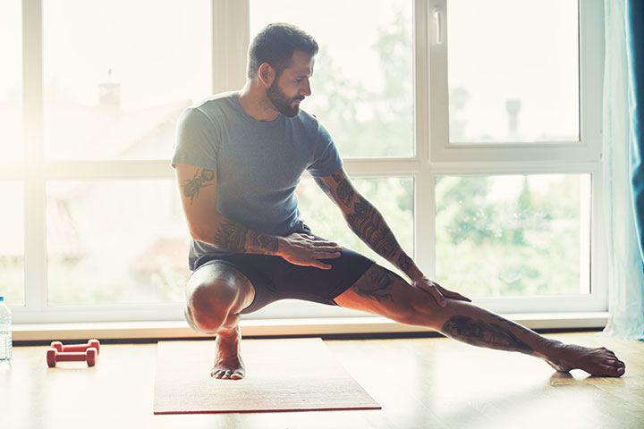 man stretching at home with fitness mat
