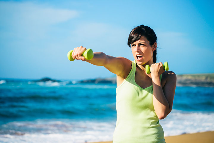 woman on beach exercising with dumbbells